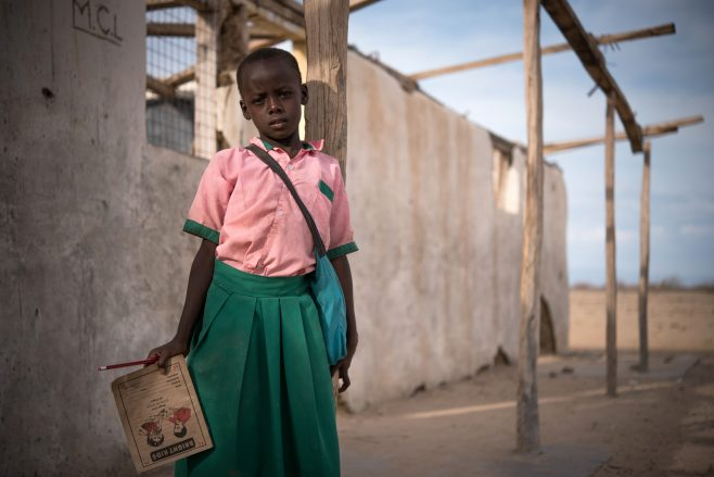 Jemima, 8 years old, at her primary school, in Turkana, Kenya.  Save The Children has been working closely with the Ministry of Education in implementing a Potu Dang Loskul (Let us all go to School) Project at Jemima's primary school. This focuses on the factors which might push children out of school and sets about making the learning environment as friendly as possible. In collaboration with the Parents Board of Management at the school, issues of positive discipline and the overall importance of education have been addressed and relayed to the wider community. The community has been made aware of how transformative education can be for marginalised children. The project has also supported the improvement of the learning environment including the construction of a classroom and better lighting in the school.  More young girls in this region, such as Jemima, are now enrolled in schools, which opens up their opportunities for the future. Girls in education are less likely to have teen pregnancies or early marriages. Traditionally, girls have been kept at home to tend to the livestock instead of enrolling in education but these traditions are gradually being broken. Strategies are also in place to assist families who may have lack of funds to pay for uniforms and other school essentials.  The Board of Management is in charge of school administration; overseeing planning, implementation of school development plans, and resource mobilisation. They are actively involved in community sensitisation on importance of education aimed at improving enrolment and education status in the community. The Board of Management is widely accepted by the community as a school management structure, and it comprises of 16 members, who are elected by parents during an annual general meeting. The head teacher is the secretary of the BoM and the area chief and any expert within the community can be co-opted as ex-officials. Election is overseen by the Ministry of Education officials.